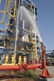 L'eau de pulvérisation de tuyau d'incendie sur la raffinerie d'essence Photo stock