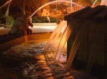 L'eau de pulvérisation de fontaine de statue de grenouilles la nuit dans les lumières chaudes jaunes en parc de Holon Herzel images libres de droits