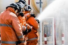 L'eau de pulvérisation de sapeurs-pompiers au feu de forêt images libres de droits