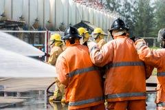 L'eau de pulvérisation de sapeurs-pompiers au feu de forêt photos libres de droits