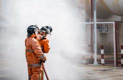 L'eau de pulvérisation de sapeurs-pompiers au feu de forêt photographie stock libre de droits