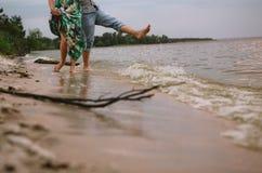 L'eau de rivage de jeu de couples éclabousse des vêtements d'amour Photos stock