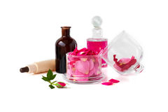 L'eau de Rose et pétrole rose, pétales de Damascène de Rose sur le fond blanc Image libre de droits