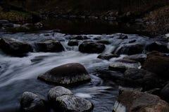 L'eau de ruisseau emballant par les roches Photographie stock