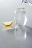 L'eau de scintillement en verre étant versé Photographie stock