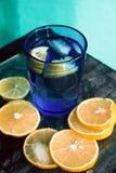 L'eau de scintillement, soude ou un genièvre et un tonique en verres colorés avec le citron et la glace Photo stock
