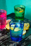 L'eau de scintillement, soude ou un genièvre et un tonique en verres colorés avec le citron et la glace Photos stock