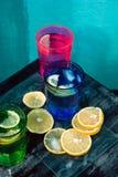 L'eau de scintillement, soude ou un genièvre et un tonique en verres colorés avec le citron et la glace Images libres de droits