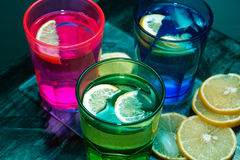 L'eau de scintillement, soude ou un genièvre et un tonique en verres colorés avec le citron et la glace Image stock