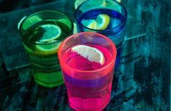 L'eau de scintillement, soude ou un genièvre et un tonique en verres colorés avec le citron et la glace Photo libre de droits