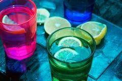 L'eau de scintillement, soude ou un genièvre et un tonique en verres colorés avec le citron et la glace Image libre de droits