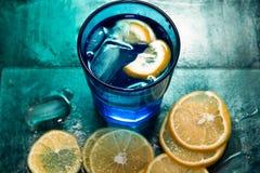 L'eau de scintillement, soude ou un genièvre et un tonique en verres colorés avec le citron et la glace Photographie stock
