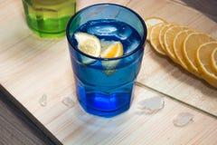 L'eau de scintillement, soude ou un genièvre et un tonique en verres colorés avec le citron et la glace Images stock