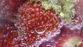 L'eau de seltz en verre avec des glaçons et des fraises, écran de centre Augmentation p?tillante de bulles banque de vidéos