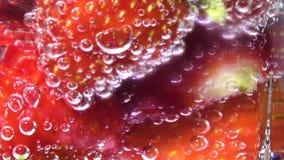 L'eau de seltz en verre avec des glaçons et des fraises, écran de centre Augmentation p?tillante de bulles clips vidéos