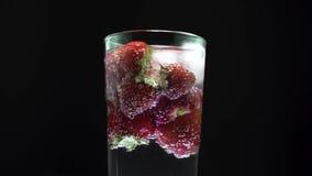 L'eau de seltz en verre grande avec des glaçons et des fraises, écran de centre Augmentation p?tillante de bulles clips vidéos