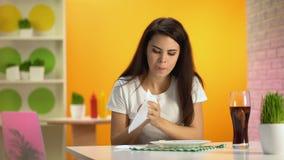 L'eau de seltz potable de jeune femme après café se reposant de repas, aliments de préparation rapide mangeant avec excès banque de vidéos