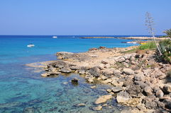 L'eau de turquoise de la mer Méditerranée avec des pierres, des bateaux et le rivage Photographie stock libre de droits