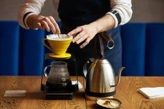 L'eau de versement de barman sur le marc de café avec le filtre de papier photos libres de droits