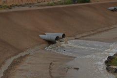 L'eau de versement de barrage noir d'Aroyo que le drainage siffle un jour pluvieux photographie stock libre de droits