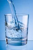 L'eau de versement dans le verre sur le fond bleu photo libre de droits