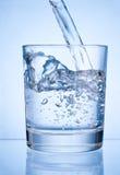 L'eau de versement dans le verre sur le fond bleu photographie stock libre de droits