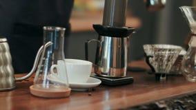 L'eau de versement de barman sur le marc de café avec le filtre Images stock