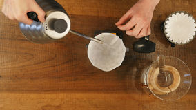 L'eau de versement de barman sur le marc de café avec le filtre Image libre de droits