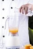 L'eau de versement de chef dedans au mélangeur électrique Images stock