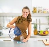 L'eau de versement de femme au foyer dans le verre du broc de filtre d'eau Photographie stock libre de droits