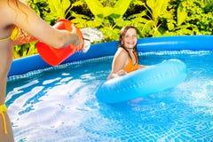 L'eau de versement de fille du seau rouge au-dessus de son ami Photo libre de droits