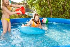 L'eau de versement de fille mignonne au-dessus de son ami dans la piscine Image libre de droits
