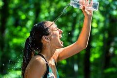 L'eau de versement de fille sur le visage après séance d'entraînement Photo libre de droits