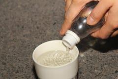 L'eau de versement de la bouteille dans la tasse pour la part bonne Image stock