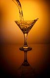 L'eau de versement de la bouteille dans le verre sur le fond orange Photographie stock libre de droits
