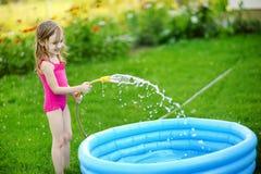 L'eau de versement de petite fille dans une piscine Photo libre de droits