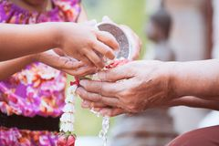 L'eau de versement de fille asiatique de petit enfant sur des mains d'un aîné plus âgé Photo stock