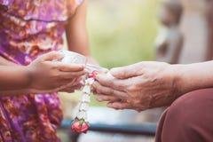 L'eau de versement de fille asiatique de petit enfant sur des mains d'un aîné plus âgé Photos libres de droits