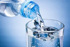 L'eau de versement de la bouteille dans le verre sur le fond bleu photo libre de droits