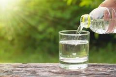 L'eau de versement de main femelle de la bouteille au verre sur le backgro de nature photographie stock