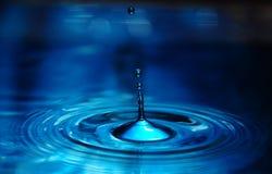 L'eau de versement sur un fond bleu Photos libres de droits