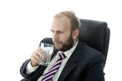 L'eau en verre de boissons d'homme d'affaires de barbe tandis que travail Photo libre de droits