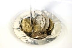 L'eau entrant au-dessus des pièces de monnaie dans le drain d'évier Photo libre de droits