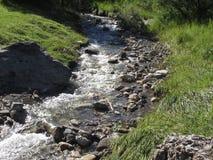 L'eau entrant et éclaboussant au-dessus des roches dans un courant de rivière de montagne photos stock