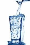 L'eau est versée dans une glace de l'eau Image libre de droits