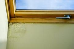 L'eau et plafond endommagé par humidité à côté de fenêtre de toit photographie stock libre de droits
