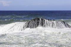 L'eau et vagues mousseuses au-dessus d'une roche en mer photo libre de droits