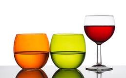 L'eau et vin - trois verres éclairés à contre-jour Fond blanc Photo stock