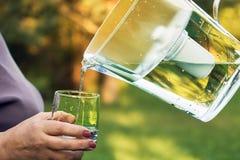 L'eau filtrée de versement d'une cruche de filtration de l'eau dans un verre qui main femelle se tenant dans le jardin d'été image stock