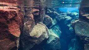 L'eau glaciaire clair comme de l'eau de roche bleue en parc national Islande de Silfra Thingvellir photo libre de droits